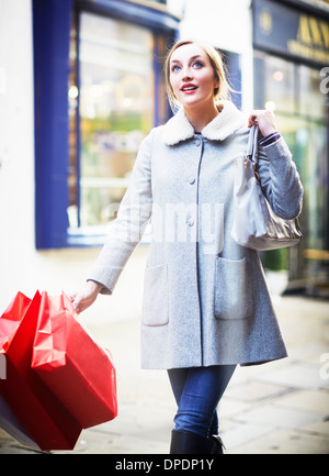 Young woman walking down street carrying shopping bag - Stock Photo