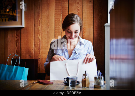 Young woman sitting in cafe looking in shopping bag - Stock Photo