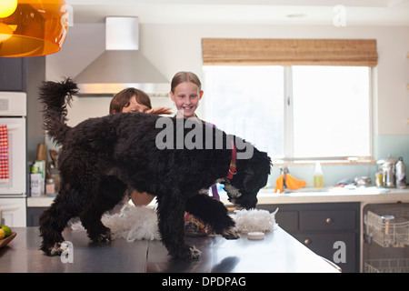 Mother and daughter playing with dog on kitchen counter - Stock Photo