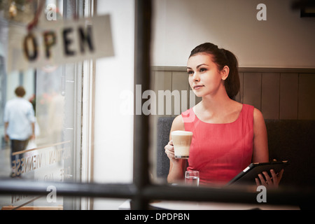 Young woman sitting in cafe with digital tablet and hot drink - Stock Photo