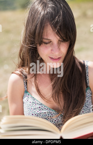 Mid adult woman reading book - Stock Photo