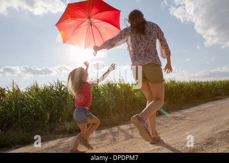 Mother and daughter walking through field carrying red umbrella - Stock Photo