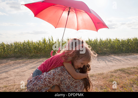 Mother and daughter hugging under red umbrella - Stock Photo