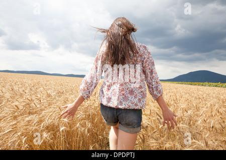 Mid adult woman walking through wheat field - Stock Photo
