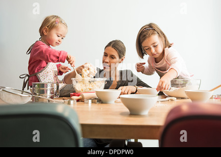 Mother and children baking, mixing batter - Stock Photo