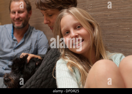 Close up portrait of daughter and parents on sofa - Stock Photo