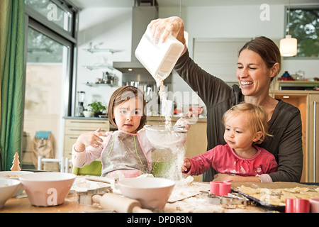 Mother and children baking in kitchen - Stock Photo