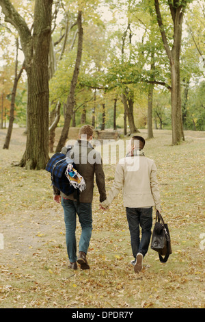 Gay couple walking in park - Stock Photo