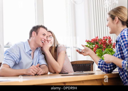 Teenage girl whispering to young man with young woman watching - Stock Photo