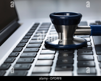 Stethoscope sitting on laptop illustrating online healthcare and doctor's desk - Stock Photo