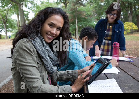 Students sitting at table in park doing homework - Stock Photo