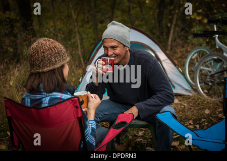 Mature couple sitting on camping chairs outside tent, drinking hot drinks - Stock Photo