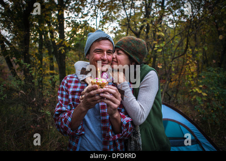 Mature couple outside tent holding birthday cupcake - Stock Photo