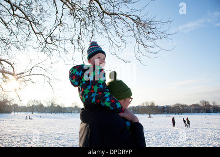 Father carrying child on shoulder in park - Stock Photo