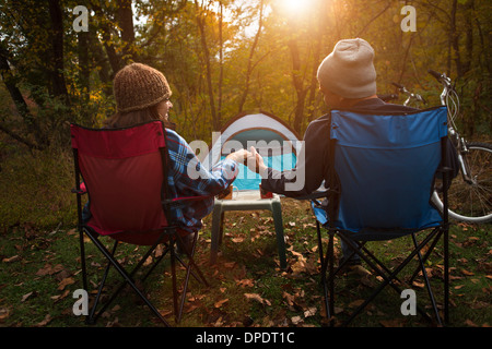 Mature couple sitting on camping chairs outside tent, holding hands - Stock Photo