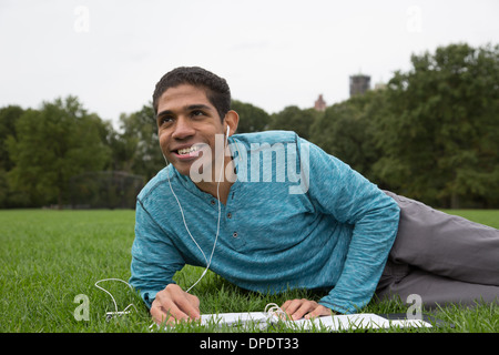 Young man lying on grass doing homework - Stock Photo