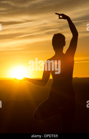 Young woman doing yoga in sunlight, Moab, Utah, USA - Stock Photo