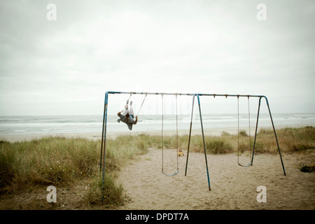 Female toddler watching father on beach swing - Stock Photo