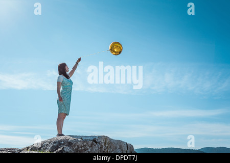 Mature woman standing on rock with golden balloon - Stock Photo