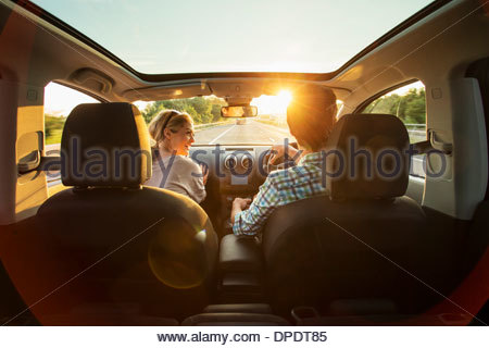 Young couple driving in car - Stock Photo