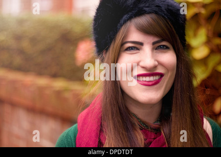 Portrait of young woman wearing winter clothing - Stock Photo