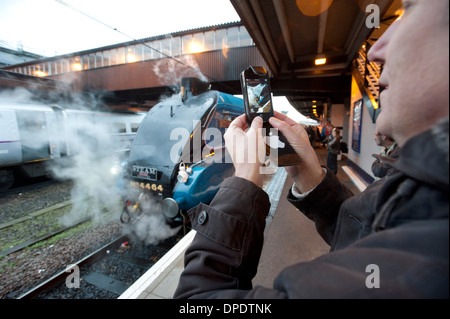 A Railway enthusiast uses his Apple iPhone to photograph a London North Eastern Railway (LNER) Class A4 steam locomotive. - Stock Photo