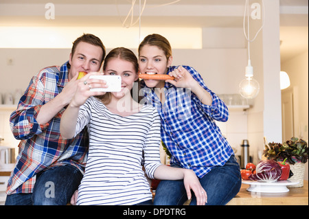 Three young people having fun taking photographs in the kitchen - Stock Photo