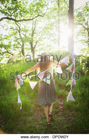Young woman walking with bunting in forest - Stock Photo