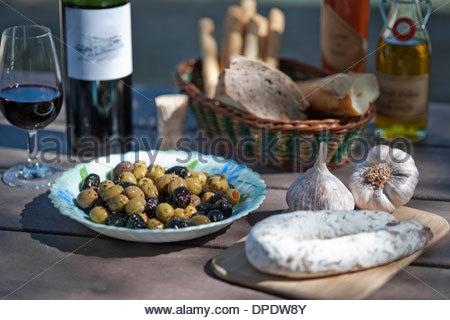 Wine, olives, sausage and traditionally french foods for picnic - Stock Photo