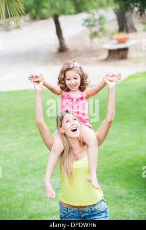 Mother carrying daughter on shoulders - Stock Photo