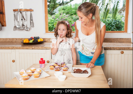 Mother and daughter decorating cupcakes - Stock Photo