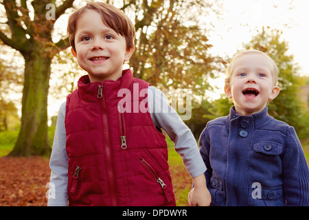 Brothers in park, holding hands - Stock Photo
