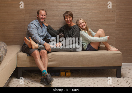 Portrait of parents and daughter on sofa - Stock Photo