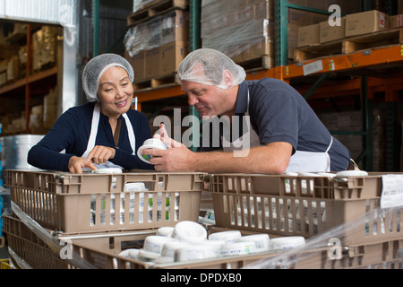 Factory workers checking products in warehouse - Stock Photo