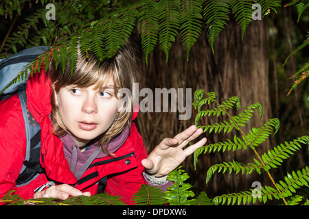 Young scared woman backpacker lost in dark forest , New Zealand - Stock Photo