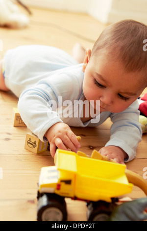 Baby lying on front playing with blocks and truck - Stock Photo
