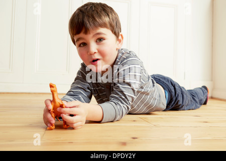 Boy lying on front playing with toy dinosaur - Stock Photo