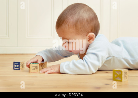Baby lying on front playing with building blocks - Stock Photo