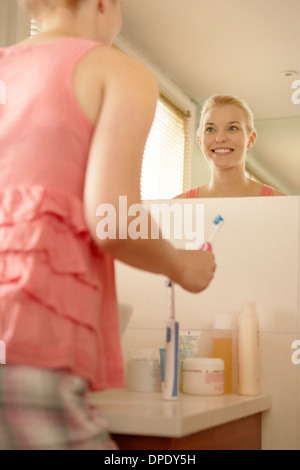 Young woman in bathroom brushing teeth