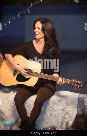 Young woman playing guitar at rooftop party - Stock Photo