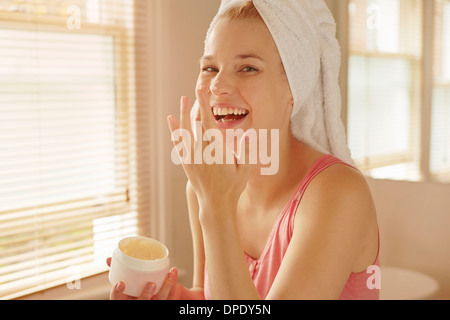 Young woman in bathroom putting on face cream - Stock Photo