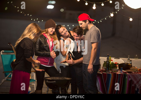 Young adult friends keeping warm at rooftop party - Stock Photo