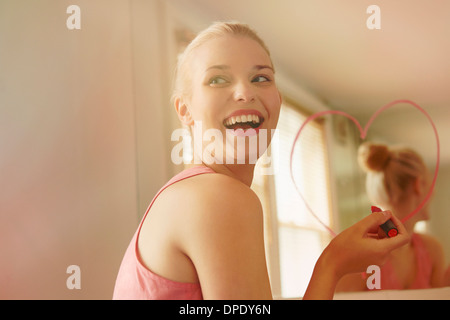 Young woman in bathroom drawing heart shape on mirror with lipstick - Stock Photo