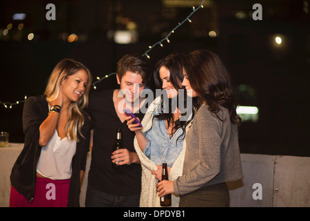 Young adult friends looking at mobile phone at rooftop party - Stock Photo