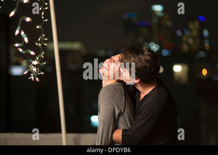 Young couple embracing at rooftop party - Stock Photo
