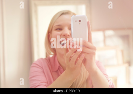 Young woman taking self portrait photograph using smartphone - Stock Photo