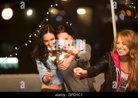 Female friends with sparklers at rooftop party - Stock Photo