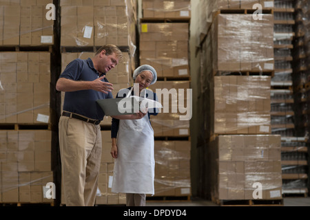 Factory worker and manager looking at clipboard in warehouse - Stock Photo