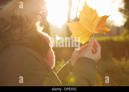 Portrait of young woman in park, holding autumn leaf - Stock Photo