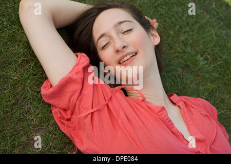 Portrait of young woman relaxing on grass - Stock Photo